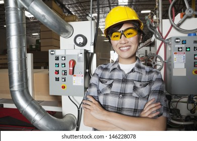 Portrait of female industrial worker smiling while standing in factory with machines in background