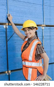 Portrait of female industrial worker standing by stacked wooden planks