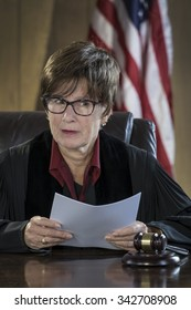 Portrait of a female judge reading a verdict in court