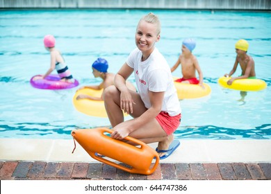 Portrait of female lifeguard holding rescue can while children swimming in pool