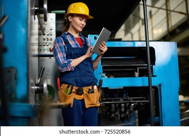 Portrait Of Female Machine Operator Using Digital Tablet While Working With  Power Units In Modern Factory