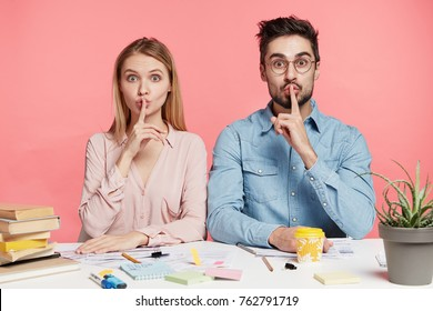 Portrait of female and male office workers or students show silence sign ask to be quiet as there is meeting in next room, works with papers and documments, prepare business report together.