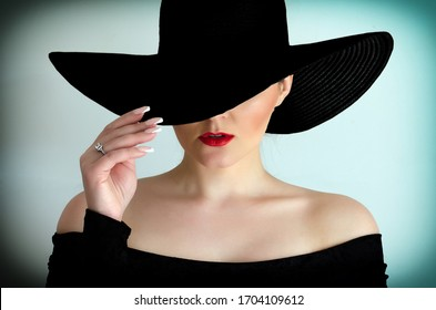 Portrait of a female model in a black hat on a white background