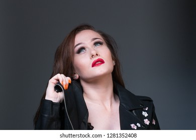 Portrait of female model. low key image in studio. black leather jacket and dark background. Sexy sultry woman.
