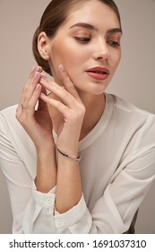 Portrait of female model with perfect makeup presenting silver bracelet and engagement ring. Crop of young woman posing in studio, isolated on gray background. Concept of jewellery.