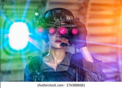 Portrait of female modern army special forces soldier, anti terrorist squad fighter, elite commando warrior using four-eyed night vision goggles in dark background