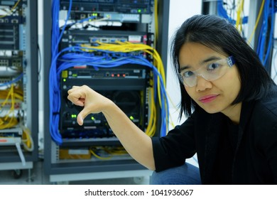 portrait female network administrator frown, stress face in a technology data center room. mission fail concept.