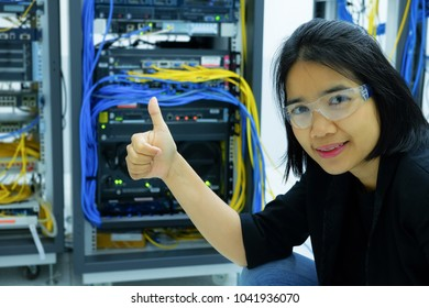 portrait female network administrator smile in a technology data center room. mission completed concept.