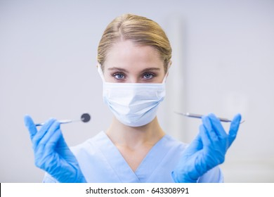 Portrait of female nurse holding dental tools in clinic