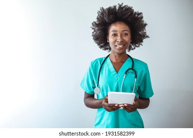Portrait of female nurse using tablet at hospital. Female nurse or doctor smiles while staring out window in hospital hallway and holding digital tablet with electronic patient file