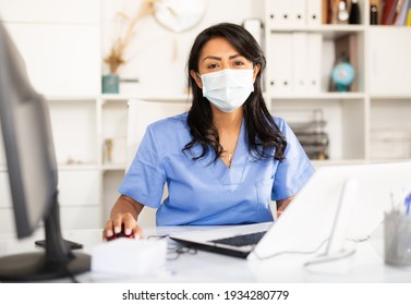 Portrait of female nurse wearing face mask sitting at doctor room and chechking appointments in her laptop