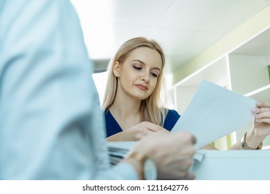 Portrait of female nurse working with documents in hospital