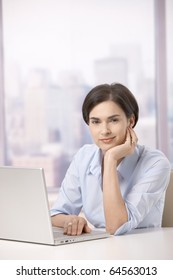 Portrait of female office worker sitting at table with computer, smiling at camera.