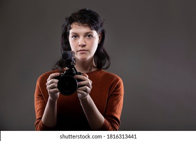 Portrait of a female online content creator holding a video camera used for vlogging.  She is an amateur filmmaker or an art student