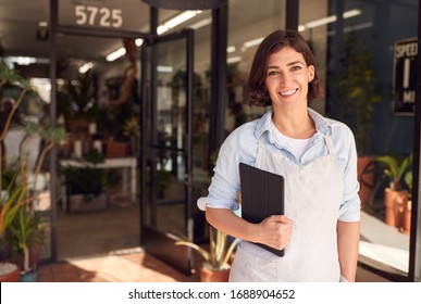 Portrait Of Female Owner Of Florists With Digital Tablet Standing In Doorway Surrounded By Plants