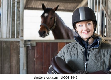 Portrait Of Female Owner Holding Saddle In Stable With Horse