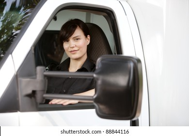 Portrait of a female paramedic in the drivers seat of an ambulance