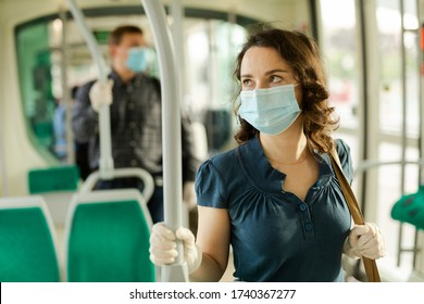 Portrait of female passenger in disposable medical mask and rubber gloves holding on handrails in urban bus. Concept of forced city trip in context of coronavirus pandemic