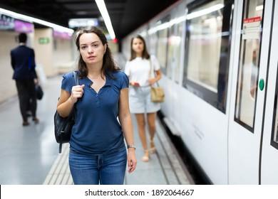 Portrait of female passenger waiting for train on subway platform ..