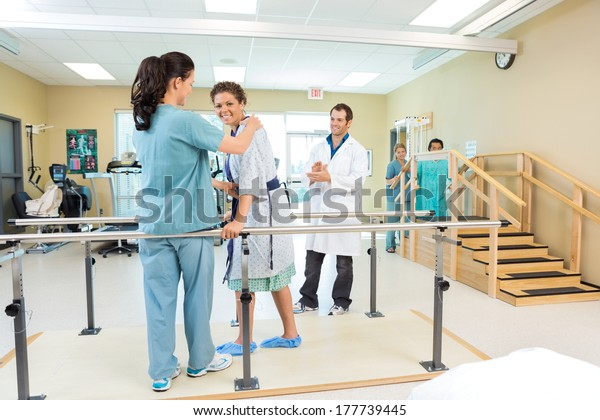 Portrait of female patient being assisted by physical therapist while doctor applauding