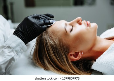 Portrait of female patient having modern noninvasive procedure of rhinoplasty, Doctor injects substance in patient nose, Aesthetic corrective treatments concept