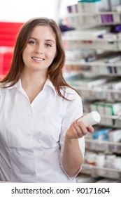 Portrait of female pharmacist holding medication container