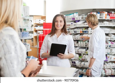 Portrait of female pharmacist holding tablet PC while attending customer on the counter