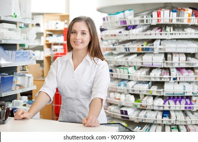 Portrait of female pharmacist standing at counter in pharmacy