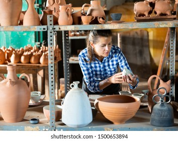 Portrait of female potter holding and inspecting ceramics in pottery workshop