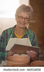 Portrait of female potter using digital tablet in pottery workshop