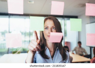 Portrait of a female professional looking at some sticky notes glued to a glass wall in the office