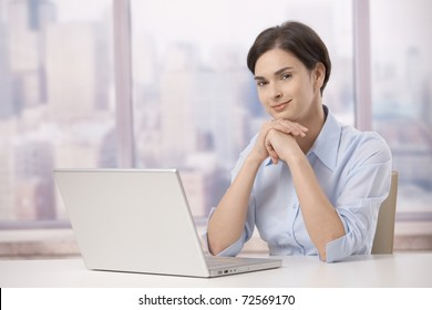 Portrait of female professional sitting at skyscraper office table with laptop computer, smiling at camera.?