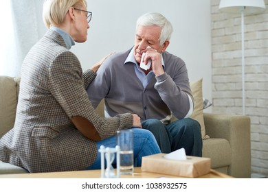Portrait of female psychiatrist comforting senior man crying during therapy session, copy space