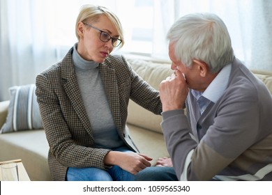 Portrait of female psychiatrist comforting senior man crying during therapy session