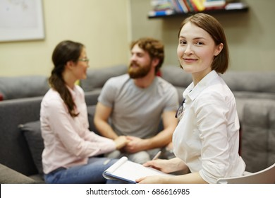 Portrait of female psychiatrist turning back to look at camera smiling during meeting with young couple for counseling therapy
