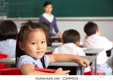 Portrait Of Female Pupil Working At Desk In Chinese School Classroom