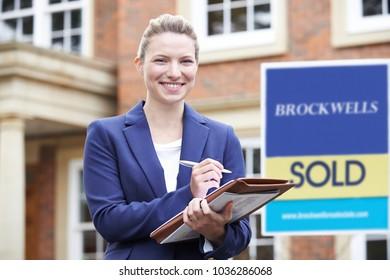 Portrait Of Female Realtor Standing Outside Residential Property