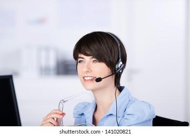 Portrait female representative listening through headphone at work