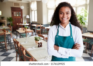 Portrait Of Female Restaurant Manager In Empty Dining Room