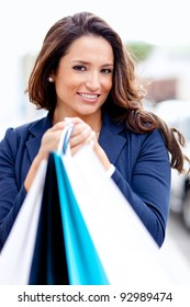 Portrait of a female shopper holding bags and smiling