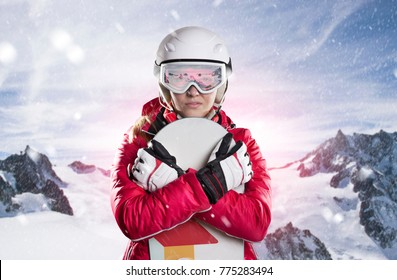 Portrait of a female snowboarder in a red winter jacket and gloves with helmet and ski goggles in front of a winter landscape with fresh snow