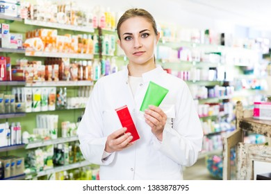 Portrait of female specialist who is holding medicines near shelves in pharmacy