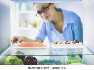 Portrait of female standing near open fridge full of healthy food, vegetables and fruits. Portrait of female