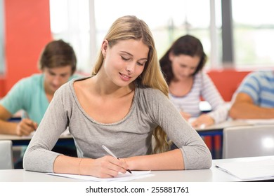 Portrait of female student writing notes in classroom
