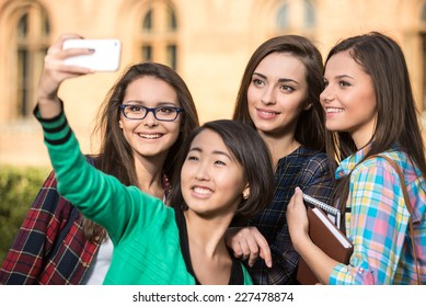 Portrait of female students that are making pictures with university building in the background.