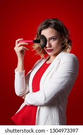Portrait of female stylist standing with makeup brush over red background
