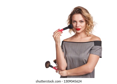 Portrait of female stylist standing with makeup brushes over white background posing
