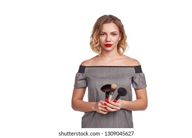 Portrait of female stylist standing with makeup brushes over white background