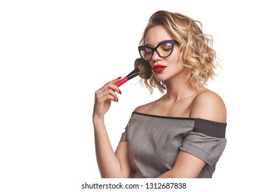 Portrait of female stylist standing with makeup brush over white background posing