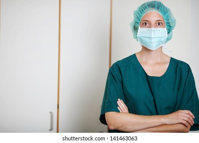 Portrait of female surgeon with arms crossed standing in hospital